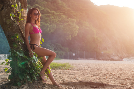 area sexy: Sexy slim young female model wearing bikini and sunglasses posing leaning against tree trunk in green mountainous area.