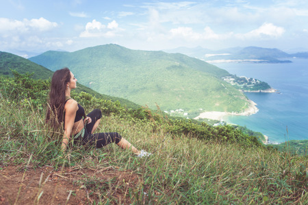 women sitting: Young fitness woman in sportswear resting after exercising or running sitting on grassy mountain peak and looking at sea landscape