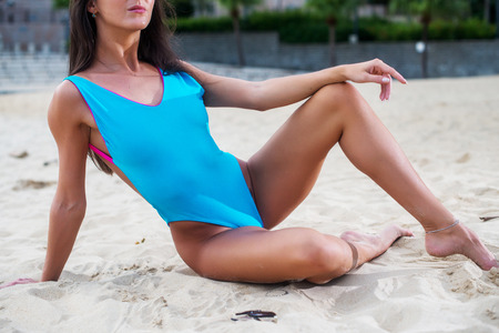 sunburnt: Cropped image of fit slender female body in swimsuit on the beach. Stock Photo