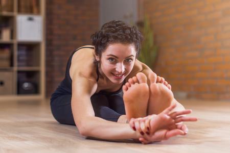裸足彼女の背中と前方のカメラ目線を曲げ床に足を伸ばして座っているかなりヨーロッパの女性
