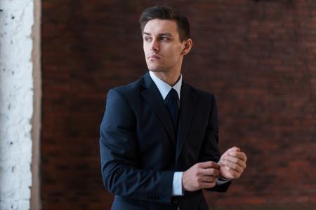 retardation: Businessman wearing wrist watch standing near office window looking away