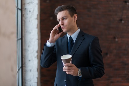 businessman waiting call: Young man talking on his mobile phone in office. Stock Photo