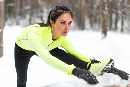 hamstrings: Winter training Fitness model athlete girl warm up stretching her hamstrings, leg and back. Stock Photo