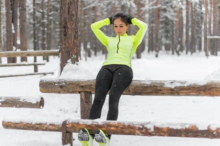 situps: Fit woman doing sit ups working out on abdominal muscles exercising to improve core muscle strength cross training outdoors winter park.