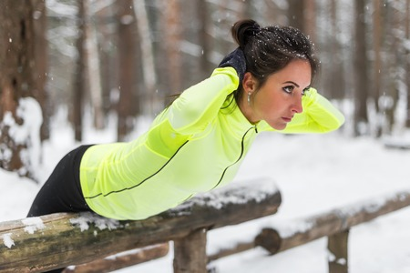 Fit woman doing back extension exercise outdoors in woods. Female sports model exercising outdoor winter park