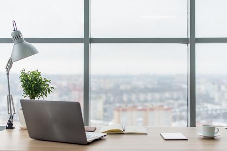 Local de trabalho com laptop notebook Mesa de trabalho confortável nas janelas do escritório e vista da cidade. Foto de archivo