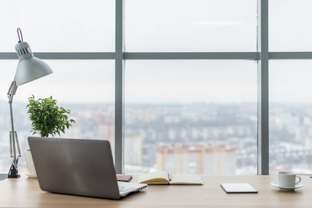 Poste de travail avec un ordinateur portable notebook confortable table de travail dans les fenêtres de bureau et vue sur la ville. Banque d'images