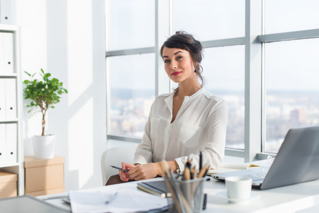 Close-up portrait of a woman sitting in modern loft office, smiling, looking at camera. Young confident female business worker ready for the work day. Stock Photo