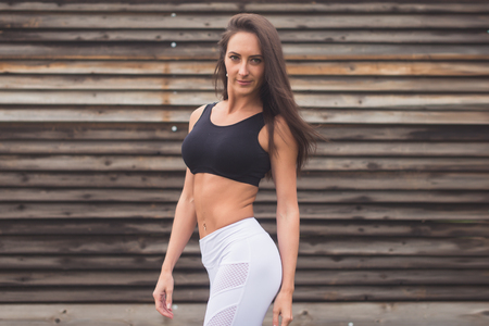 activewear: Fashion portrait of a young athletic fit girl in sportswear outdoors. Woman with perfect body Fitness concept.