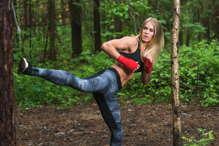 punched out: Fit woman doing kickboxing training, exercising, working out outdoors Stock Photo