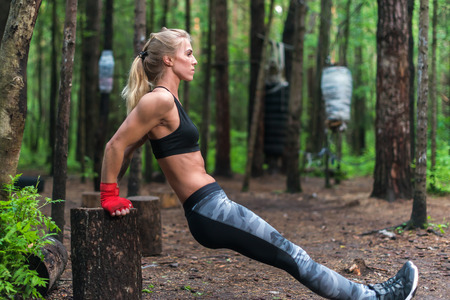 Woman exercising working out triceps and biceps doing dips with own bodyweight