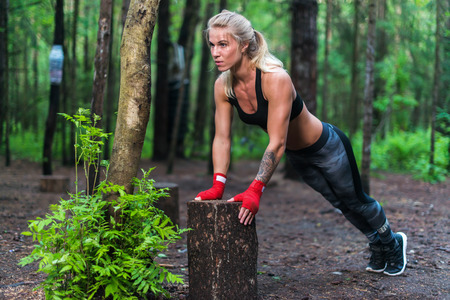 Muscular woman doing push-ups at park street work out