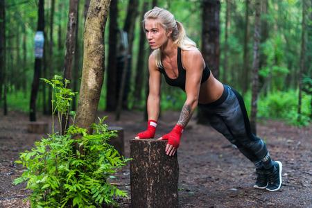 Spiervrouw doet push-ups op park straat uit te werken Stockfoto