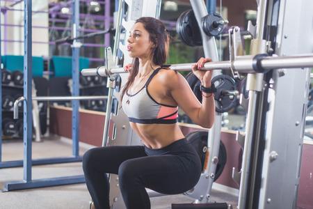 Ajustar mujer haciendo sentadillas con pesas en el gimnasio.