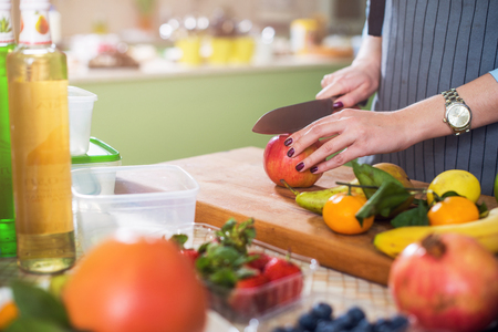storing: Hands cutting an apple on chopping board. Young woman preparing a fruit salad in her kitchen