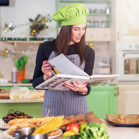 good food: Pretty young female cook wearing Chef s hat looking for a recipe in cookbook standing in the kitchen