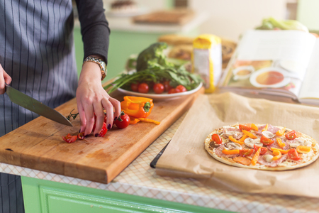 close up food: Close-up view of young woman s hands cutting vegetables on board for pizza according to recipe book