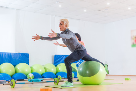muscle toning: Active middle-aged woman working out with stability ball taking part in group fitness class Stock Photo