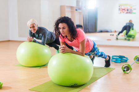 Deux sportives joyeuses s'entraînant avec un ballon suisse en train de faire de la planche dans la salle de sport