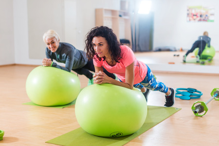 Two happy sportswomen exercising with a Swiss ball doing plank exercise in gym