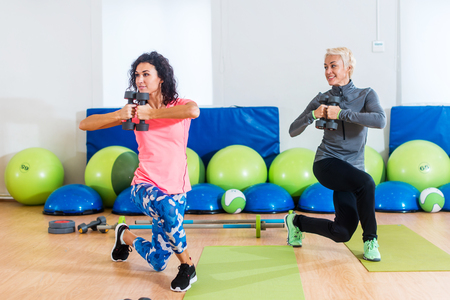 curtsy: Fit female sportswoman doing curtsy lunge exercise with dumbbells in group fitness studio class Stock Photo