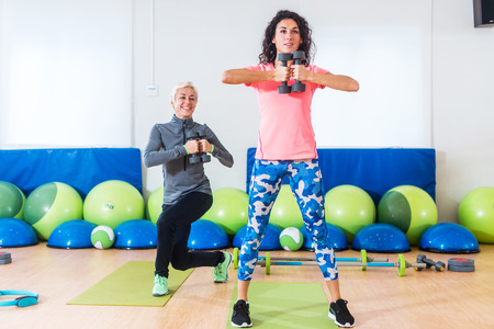 curtsy: Two Caucasian women doing exercises with dumbbells working out indoors in aerobics class
