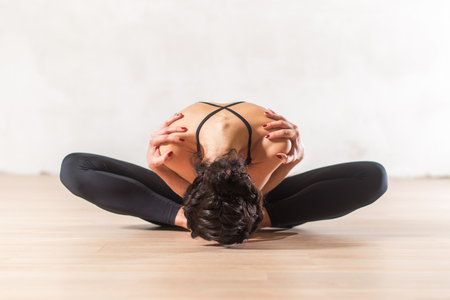Dancer doing advanced butterfly stretch exercise sitting leaning forward holding shoulders. Young flexible woman  in beautiful sensual pose.