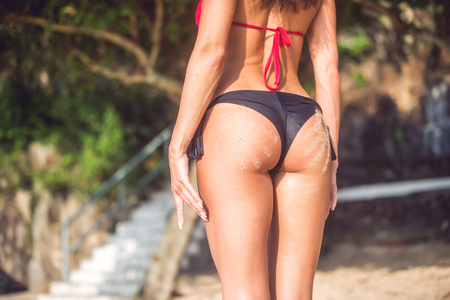Femme féminine sportive avec deux empreintes de main de sable. Cropped image de jeune femme debout son dos tourné à caméra portant bikini flou paysage naturel en arrière-plan Banque d'images - 74656658