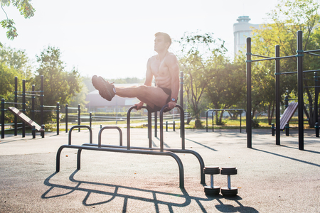 gripping bars: Young strong athlete working out in outdoor gym, doing leg lifting abs exercise. Stock Photo
