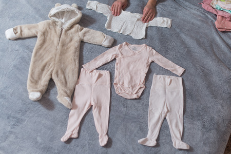 Babys clothes laid out on bed, natural light.