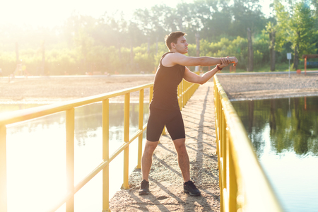 Jogger warming up exercising, stretching arms and shoulder. Fitness, sport on fresh air.