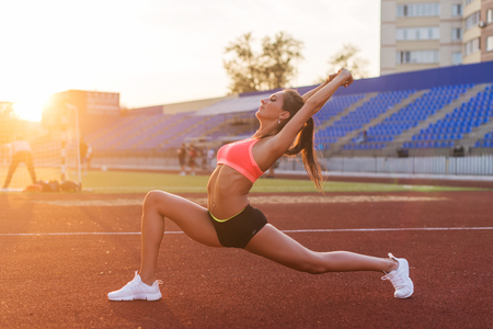 Fit woman in warrior pose stretching in stadium Stock Photo