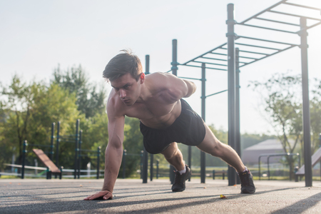 Athlete young man doing one-arm push-up exercise working out his upper body muscles outside in summer.