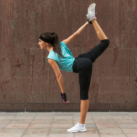 Female athlete warming up by stretching her legs outdoors. Sporty young woman doing yoga standing split exercise on the city street Stock Photo