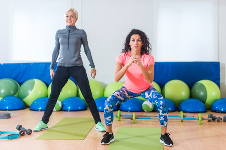 Two slim attractive sportswomen doing squat exercises during fitness class against bright equipment in gym Stock Photo