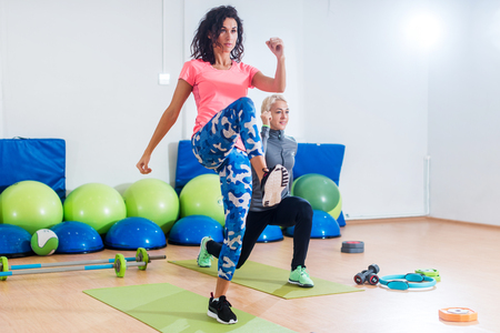 Two athletic female friends working out in a gym doing reverse lunge knee-up exercise Stock Photo