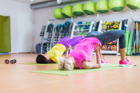 Group of women lying on floor  mats doing bridging exercise to firm buttocks indoors in fitness club
