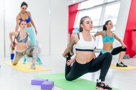 フィットネス インストラクターのスタジオのバック グラウンドで支援しながら折り敷き大腿四頭筋のストレッチ運動をしている女性のグループ 写真素材