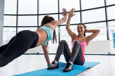 体育館でマットの上の腹筋運動をしながら彼女のパーソナル トレーナーにハイファイブを与える若い女性を笑顔に合う 写真素材