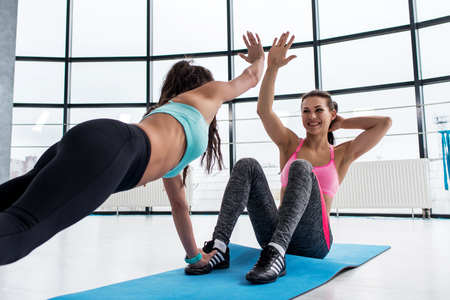 Fit smiling young woman giving high five to her personal trainer while doing abs workout on a mat in the gym Banco de Imagens - 77166181