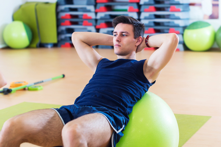 Fit man doing sit-ups on exercise balls. Stock Photo