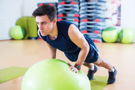 Fit man exercising with  ball workout out arms Exercise training triceps and biceps doing push ups. Stock Photo