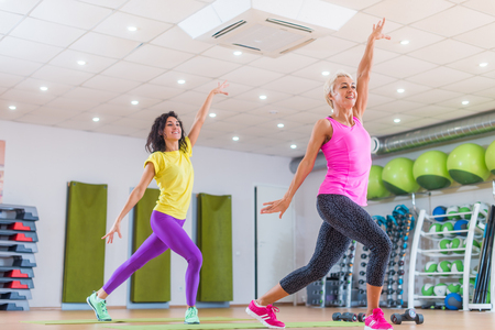 Smiling women enjoying group  dance classes in studio. Two female athletes doing aerobics indoors in gym