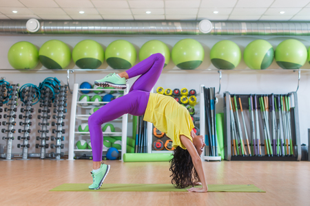 Side view of young female sportswoman doing yoga exercise standing in wheel pose in gym Stock Photo