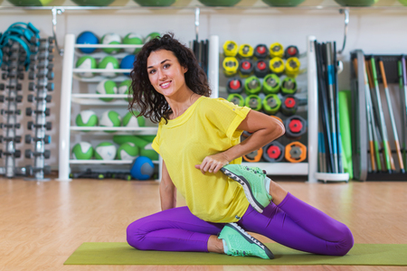 Attractive brunette young woman sitting on mat warming-up before training stretching her quadriceps in gym smiling and looking at camera