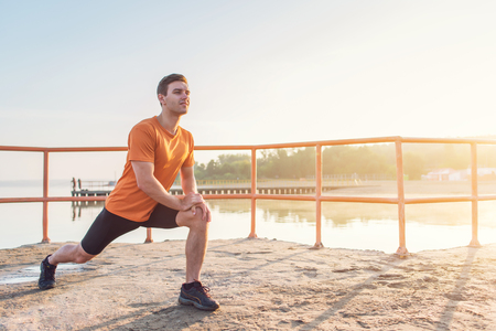 Young fit man stretching legs outdoors doing forward lunge. Stock Photo