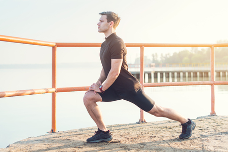 Fitness man stretching his leg muscles outdoors.
