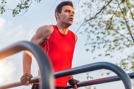 pectorals: Fit man doing triceps dips on parallel bars at park exercising outdoors