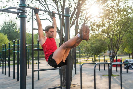 Fitnes man hanging on wall bars performing legs raises. Core cross training working out abs muscles