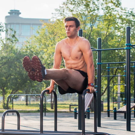 Young strong athlete working out in outdoor gym, doing leg lifting abs exercise. Stock Photo